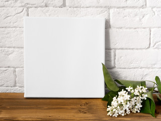 Mock up poster frame and flowers. White square canvas against a brick wall.