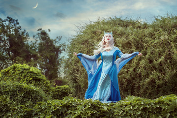 Woman elf conjures in a fairy forest, she is dressed in an antique dress.
