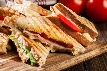Stack of panini with ham, cheese and lettuce sandwich
