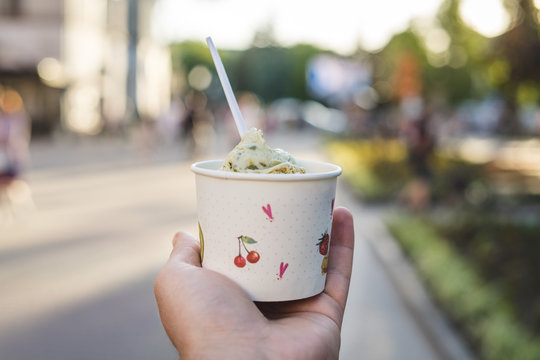 Man's hand holds paper cup with ice cream