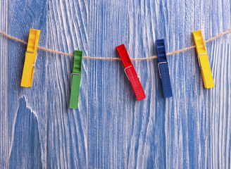 Colorful plastic clothespins on blue wooden background