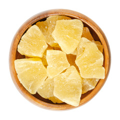 Candied pineapple pieces in wooden bowl. Crystallized chunks of Ananas comosus. Yellow colored flesh of the fruit preserved with sugar. Snack. Macro food photo close up from above on white background.