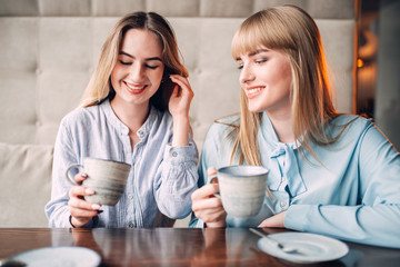 Two smiling girlfriends drinks coffee in cafe