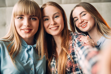 Portrait of three young smiling girlfriends