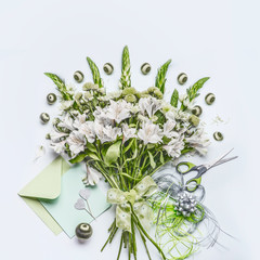 Beautiful festive bouquet  with green flowers on white desk background with envelope and paper card mock up, ribbon and scissors, top view. Holidays greeting concept