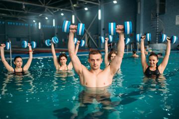 Aqua aerobics group, exercise with dumbbells