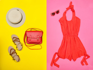 Female wardrobe. Orange overalls, handbag, brown shoes and a hat. Pink and yellow background. Fashion concept