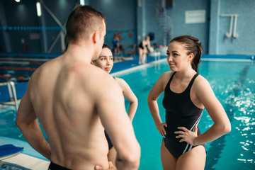 Swimmers talking on training against swimming pool