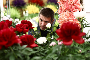 A worker adds flowers to a display as he prepares for the RHS Chelsea Flower Show in London