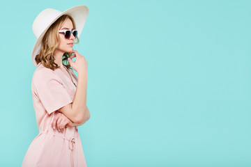 Elegant young attractive woman wearing pale pink summer dress, straw hat and sunglasses, thinking about her summer vacation. Side view of woman with hand on chin, isolated over pastel blue background.