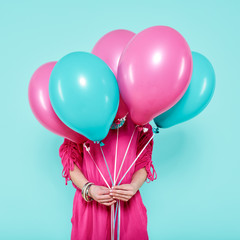 Gorgeous young woman in party outfit holding bunch of colourful balloons, isolated over pastel blue colored background. Birthday Party concept.