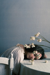 woman sleeping on table with flowers