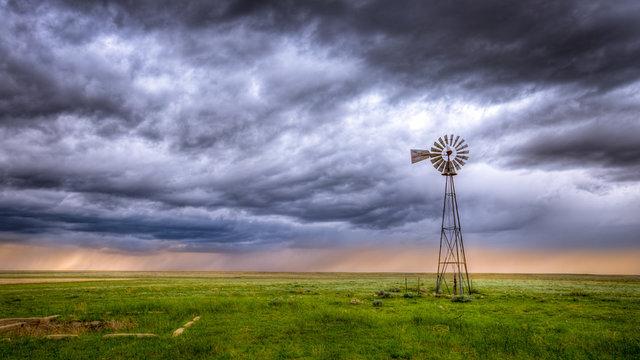 Windmill on a farm in an open field under a dramatic sky