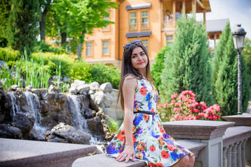 Hispanic pretty young woman rest at summer time. Latina Woman wear flowers print dress relax at nature and enjoy the life