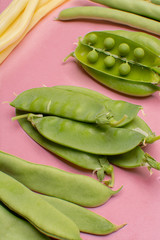 Flat lay food concept with fresh legumes,  green ripe bread beans, garden beans, sugar snaps, sweet peas, peas and yellow butter beans copy space close up isolated on pink background