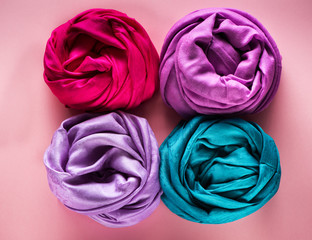 Various silk and woolen scarves on a pink background, top view