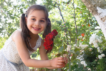 Child Girl Smelling Flowers in the Garden in Summer Season