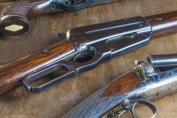 Beautiful hunting gun on wooden background close up, selective focus