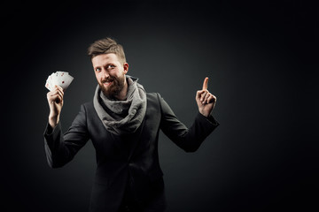 bearded stylish young handsome man holding playing cards in his hand, pointing finger and looking at the camera emotionally. dark studio background