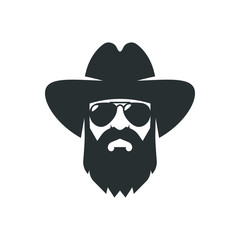 Bearded cowboy in sunglasses and in a hat. Cool American man