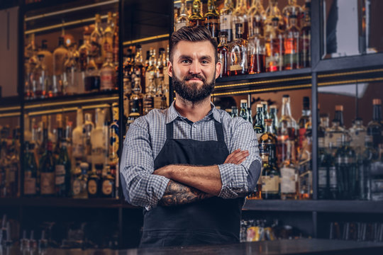 Stylish brutal bartender in a shirt and apron standing with crossed arms at bar counter background.