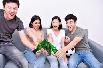 Concept of cheering. Asian teenagers watching football on television. People are cheering and winning football scores.