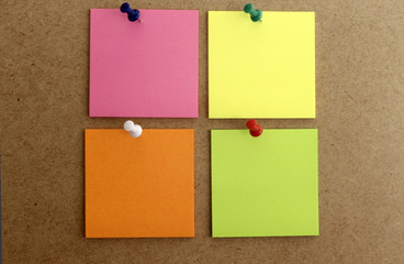 Hojas de papel cuadrada de color rosa, amarilla, y naranja . posit de colores clavados en la pared de corcho, con chinchetas de colores.