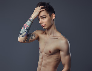 Handsome shirtless tattoed guy with stylish hair posing in a studio.