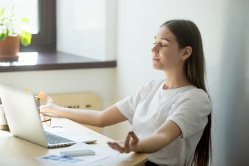 Concentrated female worker meditating in office, controlling emotions, looking for balance, relieving work stress during break. Woman sitting in chair relaxing, no pressure, mental health