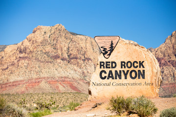 Aluminium Prints Natural Park Rock boulder sign for Red Rock Canyon in Las Vegas Nevada with mountains in the background