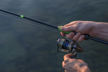 Hands of fisherman with fishing spinning rod
