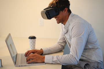 Young professional working at home, wearing virtual reality glasses. Spending a day in a VR world