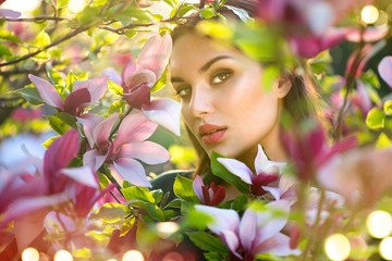 Fotoväggar - Blooming magnolia trees. Beauty young woman touching and smelling spring magnolia flowers. Happy beautiful girl enjoying nature