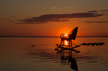 A rocking chair against the backdrop of the setting sun is in the water at Lake El'ton