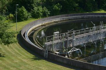 Kläranlagen Becken mit Natur und grüner Wiese im Sommer