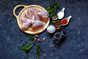 Ingredients for marinating chicken wings on a dark gray concrete background. Raw chicken wings on a wooden board, olive oil, red wine vinegar, salt, sugar, pepper, garlic, spices and herbs