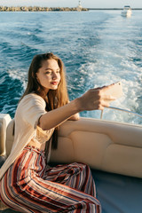 beautiful long-haired girl in trendy summer pants swims on a yacht on the Caribbean sea and makes selfie on her smartphone