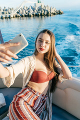an attractive young girl went on a sea voyage on a yacht, resting and making selfies on her smartphone