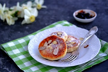 Breakfast. Curd cheese cakes with plum jam, sprinkled with powdered sugar and almonds.