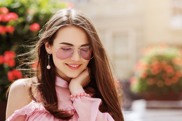 Outdoor close up portrait of young beautiful smiling girl wearing stylish pink color sunglasses, earrings, bracelet, cold shoulder blouse walking in street. Spring, summer fashion concept. Copy space