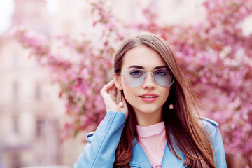 Outdoor close up portrait of young beautiful smiling girl wearing stylish blue color aviator sunglasses, earrings, jacket, posing in street. Spring, summer fashion concept. Copy, empty space for text