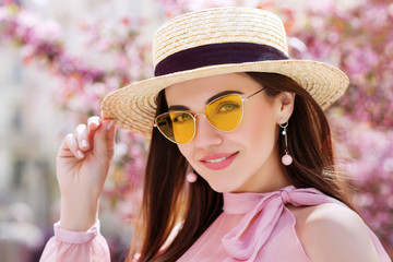 Outdoor close up portrait of young beautiful happy smiling girl wearing trendy yellow color sunglasses, straw boater hat, earrings, off shoulder pink blouse. Spring, summer fashion concept