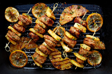 Aluminium Prints Grill / Barbecue Grilled skewers with chicken meatballs and pineapple with herbs on a grill plate. Fruit and meat skewers
