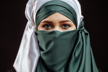 close up cropped photo of awasome Muslim girl in green hijab on the black background. submission concept