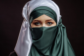 close up portrait of good-looking Muslim bride isolated on the black background. wedding idea