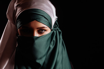 successful Muslim businesswoman isolated on the black background. copy space