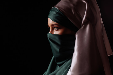 close up profile of mysterious Muslim girl isolated on the black background