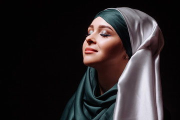 charming young Muslim woman inspired by religion.close up portrait. isolated black background. copyspace.pure soul. kindness and generosity concept