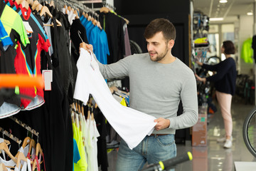 Ordinary man choosing sport shirt in shop