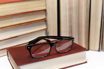 Blurred glasses and piles of books close-up.Concept bad and weak vision.